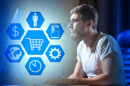 The concept of online shopping. A man in glasses and a white t-shirt enthusiastically selects products in an online store. Online sales. Purchase of products with delivery. Trade in the Internet.