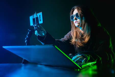 Hacker girl. Illegal receipt of other people's information. Cybercrime. Girl hacks into the program. The woman hides her face behind dark glasses.