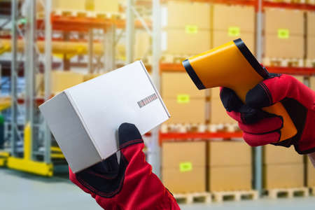 Reading a barcode from a cardboard box. Hands in work gloves hold a barcode reader and a box. Acceptance of goods to the warehouse. Product encoding.