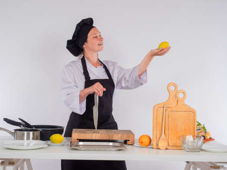A female chef with a lemon in her hand. Girl in the kitchen on a white background. A woman in a chef costume. Recipes. Cooking of the peoples of the world.