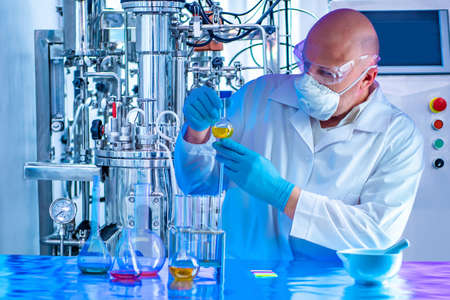 Chemist with a test tube on the background of a laboratory fermenter. Observation of the fermentation process. Laboratory equipment. Experiments in the field of pharmaceuticals. Microbiology.