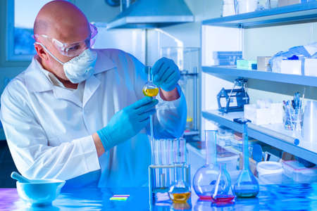 The chemist conducts research in the laboratory. A man in a protective suit and mask with a test tube in his hands. Synthesis of new substances. Analysis of samples of the chemical industry.