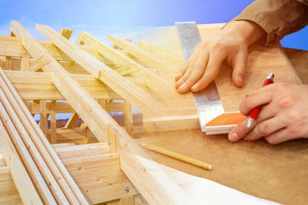 Carpentry work in construction. A man measures a wooden bar against the background of the frame of the cottage. The work of a carpenter. Construction of a wooden house.