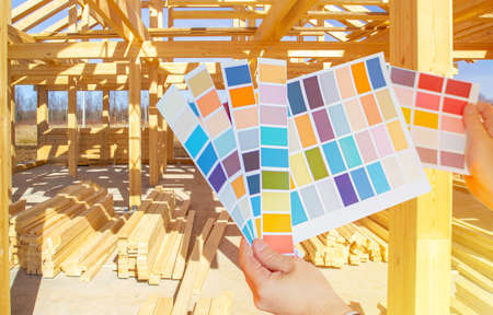 A person holds color palettes in front of a house under construction. Design project of the cottage. Color scheme for the new building. Color selection for interior and exterior finishes.