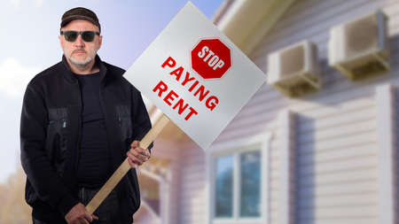 Sad man with a sign Stop paying rent on the background of the house. People put forward economic demands. The man draws attention to the difficult situation of mortgage borrowers.