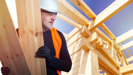 Construction of wooden houses. Carpenter on the construction site. A man in an orange vest and hard hat next to the frame of a new house. Builders with boards in their hands.