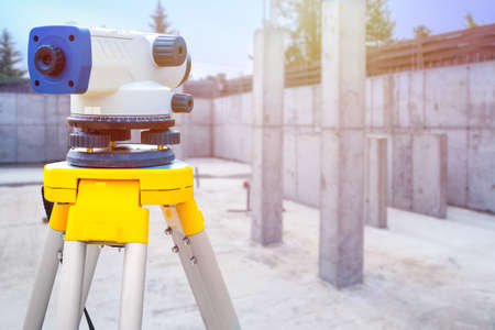 Theodolite in close-up. Theodolite on the background of the Foundation of a new house. Monitoring the absence of deviations. Measuring tool for determining angles. Theodolite on a tripod.