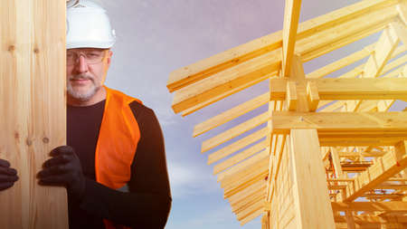 Builder with a Board in his hands on the background of the frame of the cottage. Construction of a wooden building. Delivery of lumber to the construction site. A carpenter in a hard hat.