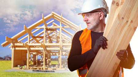 Builder with boards in his hands on the background of a cottage under construction. Carpentry work in construction. Construction of wooden houses. The supply of lumber. Zdjęcie Seryjne