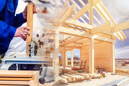 Construction of a cottage made of wood. Carpentry work on a construction site. Wood processing. Carpenter saws wood for building a house. Carpenter at work.