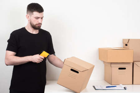 Warehouse stock. A man with a barcode reader. Marking of manufactured products. The encoding of information about the product. Marking of parcels. Reading the barcodes.
