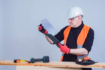 A man in a white hard hat and work gloves examines the drawings. Study of the order scheme. A man works as a carpenter. A man in an orange vest next to planks and tools.