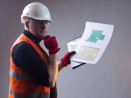 The work of an architect. The architect reflects on the layout of the premises in the building. A man in a white hard hat and a reflective vest. Builder with building plans and pencil.