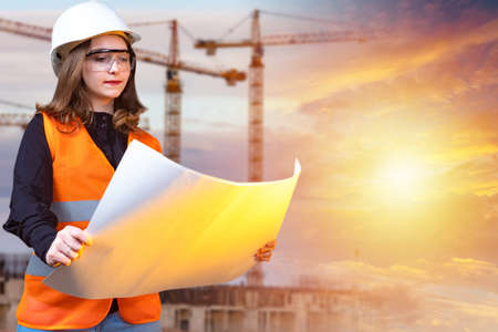 Project of a new house. A girl in a white helmet against the background of cranes and the sun. A woman studies the drawings of the future building. A girl in a reflective vest on a construction site.