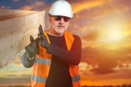 Joinery. A man carries planks on his shoulder. A man with planks against the evening sky. A carpenter in a White construction helmet and reflective vest.