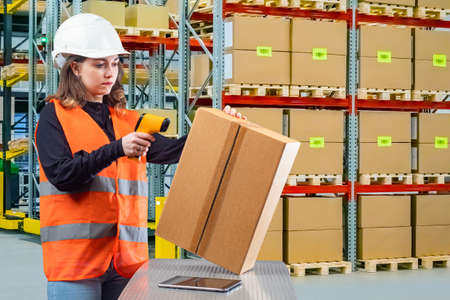 Warehouse. Storage of goods in a warehouse. The work of the storekeeper. A girl in a reflective vest reads a barcode from a box. Warehouse storage technologies. Stok Fotoğraf