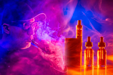 E-cigarette smoker. The concept of vaping in a smoky neon background. A man in glasses and a baseball cap smokes a VAPE. Smoker and Smoking accessories on a dark background in smoke.