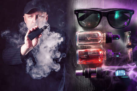 A man smokes a VAPE on a dark background. E-cigarette smoker and Smoking devices in clouds of smoke. The man lets out smoke and demonstrates an electronic cigarette. Accessories for vapers.