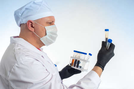 Laboratory analysis. A doctor in a white coat is holding test tubes. Blood test. Diagnosis of diseases. Work in a diagnostic laboratory. Stok Fotoğraf