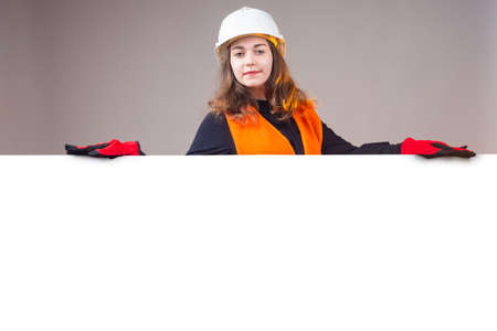 Industry, Engineer, construction concept. Young smiling Worker woman. Girl in a construction uniform. Female construction worker leans on a poster with place for text.