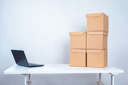 Preparing parcels for shipment. Cardboard boxes and a laptop are on the table. Home delivery of goods. Delivery service. Courier service. Delivery of purchases from online stores. 版權商用圖片