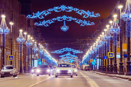 New Year Saint Petersburg. Cars go down the street decorated with garlands. Festive illumination on city street. Christmas in Russia. Winter evening in St. Petersburg. Stock Photo