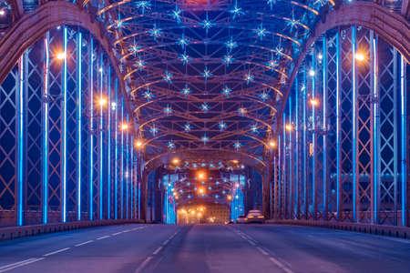 Saint Petersburg on Christmas. Bolsheokhtinsky bridge with Christmas decorations. Peter the Great bridge from the inside. Bridges Of Saint Petersburg. Night city lighting.