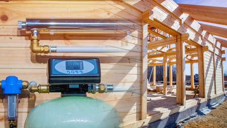 Water treatment system on the background of a cottage under construction. Sanitary-technical equipment in the new house. Water filtration. Drinking water. Engineering networks in the house.
