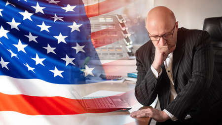 A man with a suit at a Desk against the background of the American flag. A businessman is thinking about a contract with an American firm. Business in USA. Deliveries of goods to America.