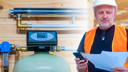 Engineer on the background of the water treatment system in the house. Engineering communications with filters. Water filtration. Purified drinking water. Engineering networks in the house. Stock fotó
