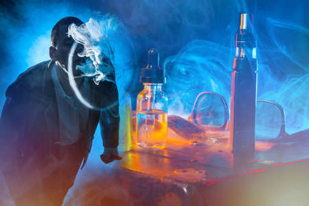 The man lets out a smoke ring from a VAPE on a dark background. The concept of Smoking electronic cigarettes. Demonstration of Smoking skills. The smoke from the vape.