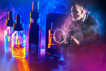 The concept of vaping on a dark background. Vaping in neon lighting. A man releases smoke from an electronic cigarette against the background of Smoking devices. VAPE shop.