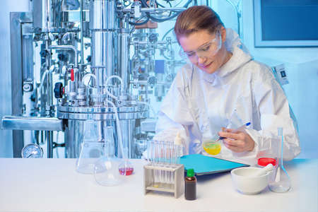 Female Chemist on the background of an industrial fermenter. The scientist records the results of the experiment next to microbiological bioreactor. Cultivation of microorganisms. Bioengineering.