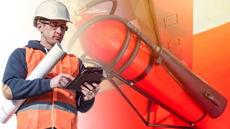 A man checks the means of extinguishing fires. Periodic inspection of fire extinguishers. Compliance with the requirements for ensuring the safety of people.
