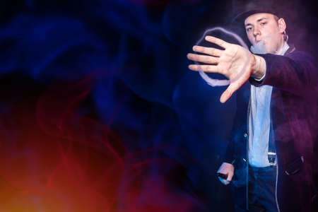The man lets out clouds of vaping steam from his mouth and stretches out his hand. The man gestures, showing a smoke ring from an e-cigarette. Smoker and smoke from a VAPE with lighting.