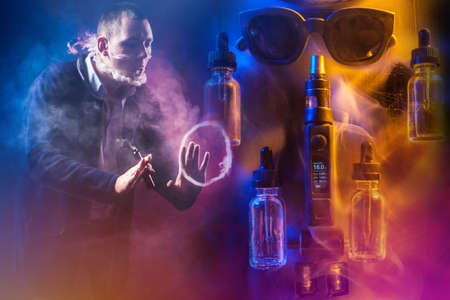 The man lets out smoke from his mouth and nose in an unusual shape. The concept of vaping. A man with a VAPE gestures against the background of gadgets for smoking. Fashion for Smoking e-cigarettes.