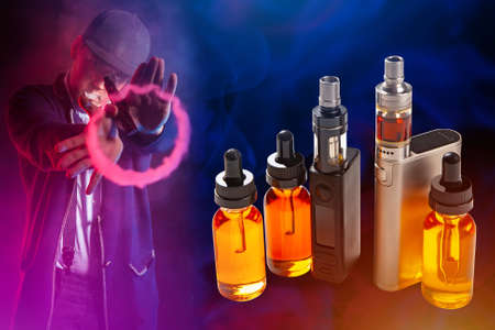 Vapes and vials with liquids on a dark background. A man smokes a VAPE and shows a ring of steam. Vaper gestures, releasing steam from his mouth. The concept of vaping.