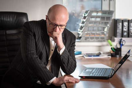 A man in glasses and a black suit ponders the information. A man in the office. A person is preparing to make an important decision. Selecting the appropriate option. Different alternatives.