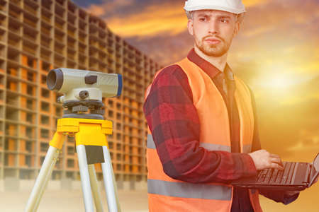 Surveyor's equipment and construction site. Measuring equipment in construction. A construction worker in a white hard hat with a laptop. A man stands next to theodolite.