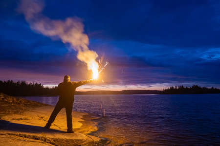 Smoke signal. A man with a smoke torch in the evening by the water. Rescue. SOS. Distress signal. The man lights a smoke signal and calls for help. A man in a life jacket on the lake shore.