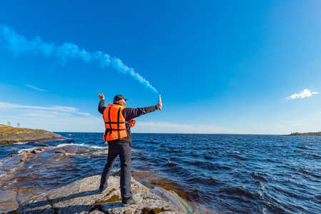 A man with a smoke torch. Salvation. SOS. Distress call. Smoke signal. A man lights a smoke signal. A man in a life jacket on the lake shore.