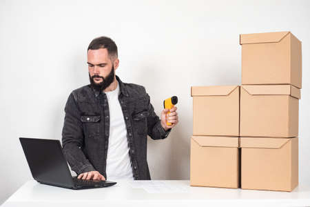 A man with a barcode reader and a laptop. Storekeeper next to cardboard boxes. Inventory. Product packaging marking. Encoding of product information.