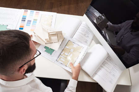 Approval of the construction project. A man sits at a Desk with a house plan, drawings, and color palettes. Project of a new house. The work of an architect. Construction engineer. Foto de archivo
