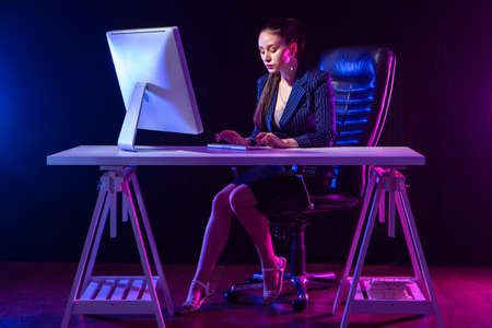 Businesswoman at work. A beautiful woman is working at a computer. A woman earns money. Portrait of a woman in a business suit on a dark purple background.