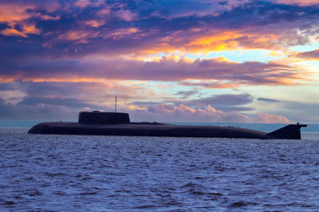 Submarine on the background of beautiful sky. Multicolored clouds over the sea and the submarine. Naval forces concept. Submarine close-up. Military fleet.