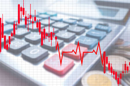 Economy. Finance. Falling chart. Lots of coins next to the calculator. Financial market. Concept - forecasts of financial analysts. Analysis of the global economy. Analysis of the economic situation
