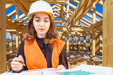 Woman builder is holding drawings of a building. Builder with papers in his hands. Concept - construction of frame houses. Construction of the cottage. Architect checks building blueprints. Girl