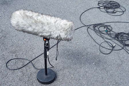 Windproof. Microphone in wind protection. Large street microphone in windproof fur. Professional equipment for video operators. Microphone stands asphalt. Concept - selling professional microphones