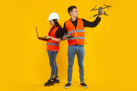 Drone in hands of builders. Guy and a girl launch a drone. Concept - shooting services with a quad copter. Workers in orange vests are filming from a drone. Guy and girl on orange background. Laptop Stock fotó