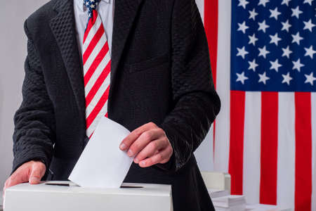 Voting box in USA. Voting president USA. Voter throws bill into election box. Man at polling station in United States. Man next to election box. Ballot urn next America flags. Presidential elections.